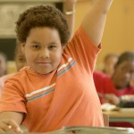 Young boy raising his hand in classroom