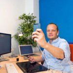A business man taking a selfie in his clean and paperless office