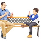 Young boy playing cards with his older cousin seated on bench is