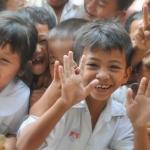 Children smiling at a camera. Mentors, mentees, youth mentoring.